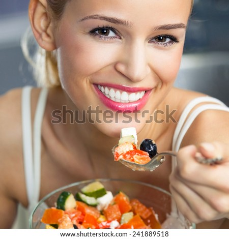 Young cheerful smiling woman eating salad  - stock photo