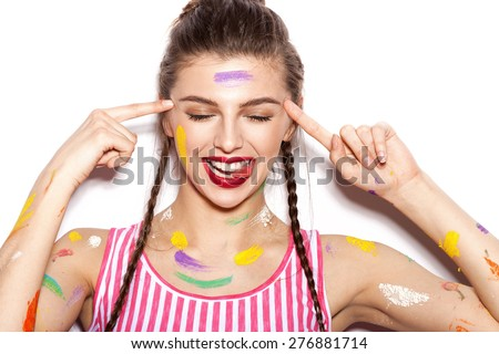 Young cheerful soiled in paint girl having fun. Smiling Woman with bright makeup and hairstyle with pigtails. White background not isolated