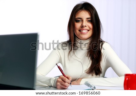 Young cheerful student doing her homework - stock photo