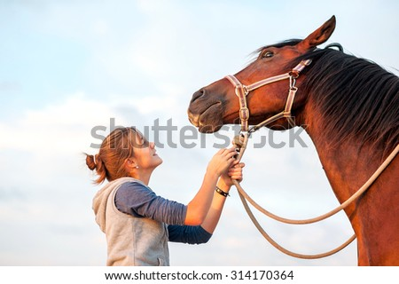 Young cheerful teenage girl calming big spirit chestnut horse. Vibrant multicolored summertime outdoors horizontal image. - stock photo