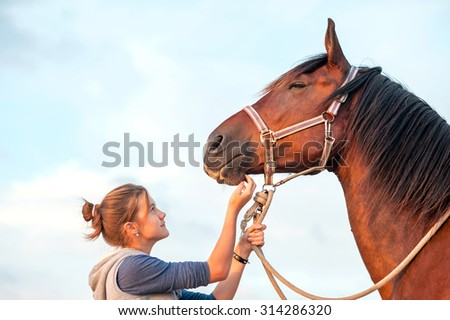 Young cheerful teenage girl stroking big chestnut horse's nose. Vibrant multicolored summertime outdoors horizontal image. - stock photo