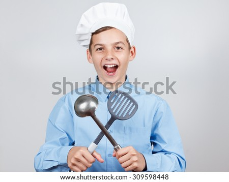 Young cheerful teenager with a ladle and humor in a chef's hat. On white background. - stock photo