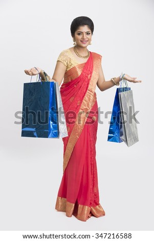 Young cheerful traditional woman with shopping bags on white background. - stock photo