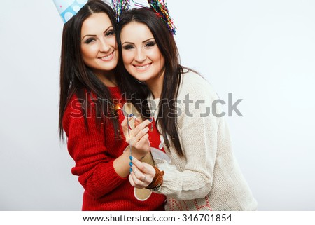 Young cheerful twins, wearing in colorful sweaters and festal hats, posing on white background with Bengal fires, in studio, waist up - stock photo
