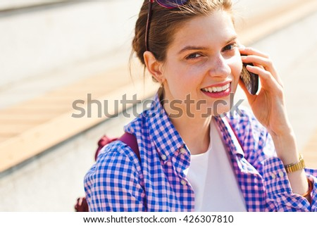 Young cheerful woman chit-chatting on a phone outdoors looking at camera. Concept of young busy woman having a lifestyle business or a student talking by a phone. Close-up view with copy space - stock photo