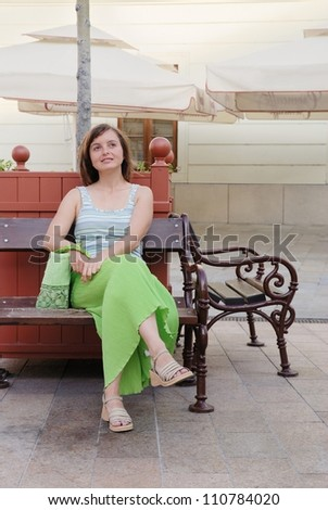 Young cheerful woman dressed in green sits on bench