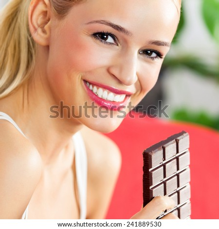 Young cheerful woman eating chocolate  - stock photo
