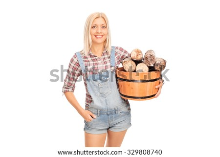 Young cheerful woman holding a bucket full of logs and looking at the camera isolated on white background - stock photo