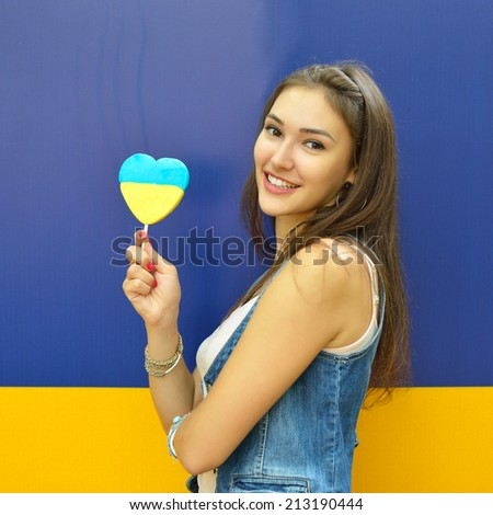 Young cheerful woman holding candy painted in colors of ukrainian flag. Ukrainian patriot concept.