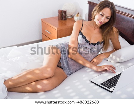 Young cheerful woman in lingerie lying in bed with laptop