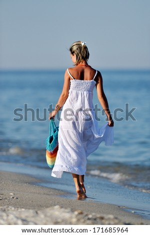 young cheerful woman on the beach in summer