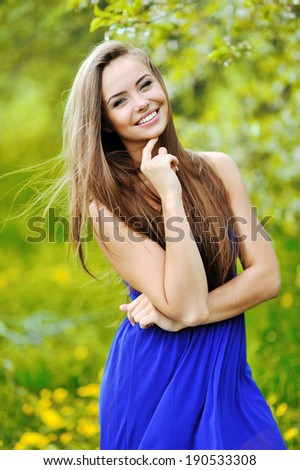 Young cheerful woman posing in a green park  - stock photo