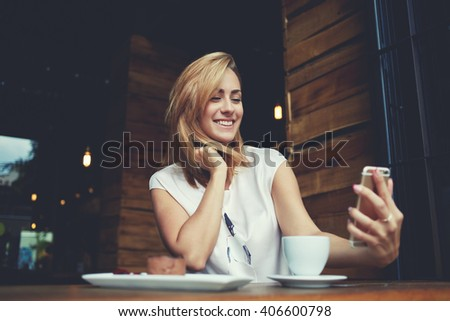 Young cheerful woman posing while photographing herself on smart phone camera for a chat with her friends, attractive smiling hipster girl making self portrait on cell telephone while sitting in cafe  - stock photo