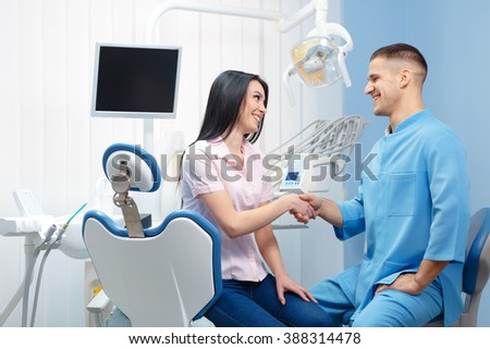 Young cheerful woman shaking hands with dentist in a dental clinic. People, medicine, stomatology and health care concept