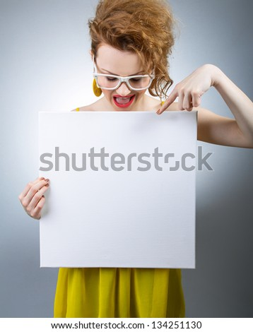 Young cheerful woman showing her finger on blank white board - stock photo