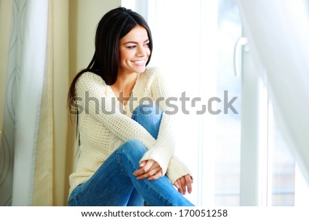 Young cheerful woman sitting on a window-sill and looking outside - stock photo