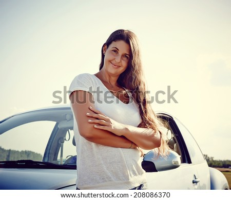 Young cheerful Woman standing in front of her new car, rental car smiling looking into camera. - stock photo