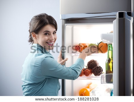 Young cheerful woman taking a green apple from refrigerator and smiling at camera. - stock photo
