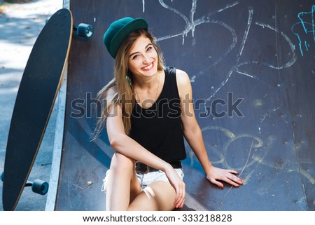 Young cheerful woman, wearing in cap, shirt and shorts, sitting on the pavement with her skateboard, on the street, waist up - stock photo
