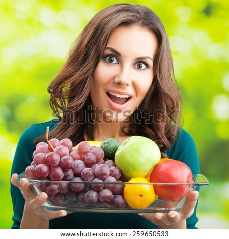 Young cheerful woman with plate of fruits, outdoors