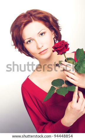 Young cheerful woman with red rose