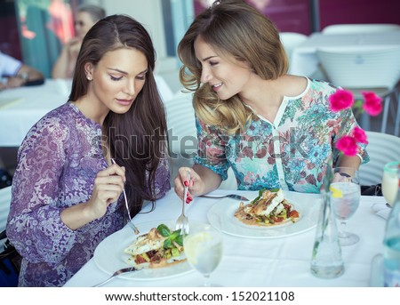 Young cheerful women on lunch at restaurant  - stock photo