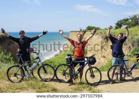 young cheering  caucasian bicyclists on the seaside - stock photo