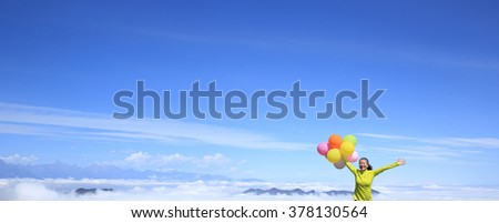 young cheering woman running with colorful balloons on mountain peak - stock photo