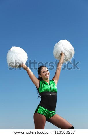 Young cheerleader in green costume jumping against blue sky