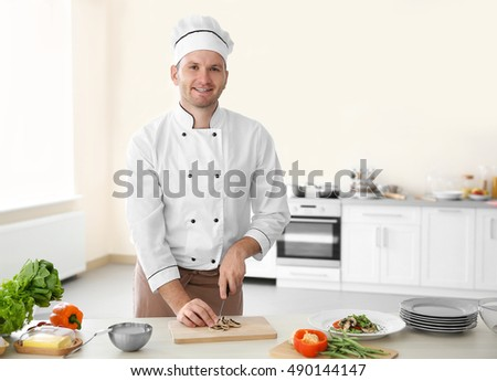 Young chef cook cutting mushrooms in kitchen
