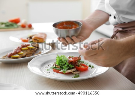 Young chef cook putting tomato sauce on dishes