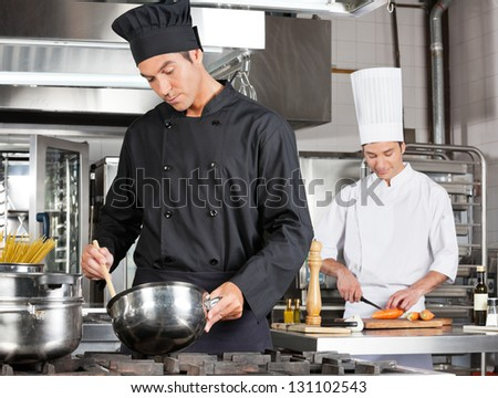 Young chef cooking food with male colleague chopping vegetable in background