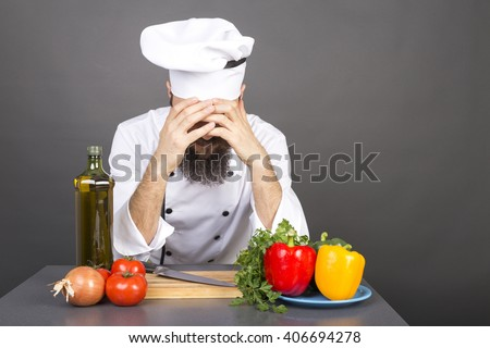 Young chef covers face with hands, having problems, isolated on gray - stock photo