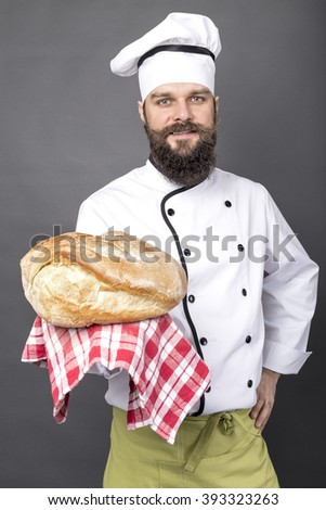 Young chef holding a big rustic bread over gray background