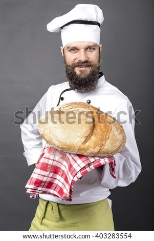 Young chef holding a big rustic bread over gray background - stock photo