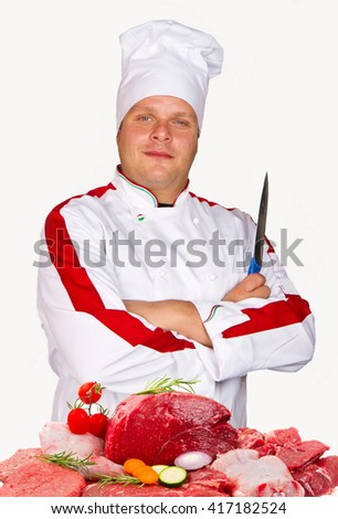 young chef holding a knife in front of an assortment of fresh meat