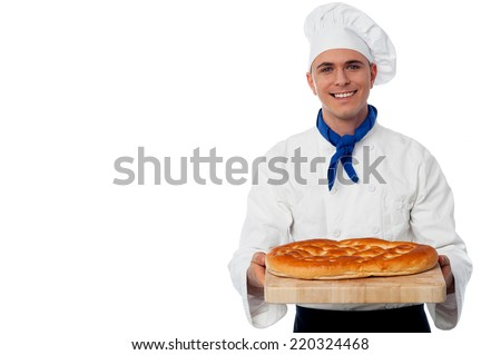 Young chef holding a loaf of fresh baked bread