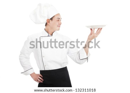 young chef holding and looking a dish - stock photo
