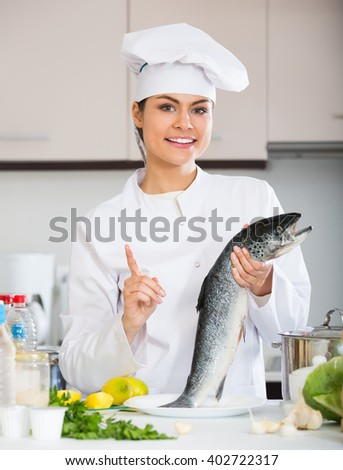Young chef holding carcass of fish in professional kitchen