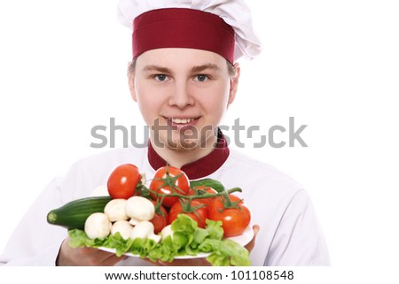 Young chef holding plate with vegetables over white background - stock photo