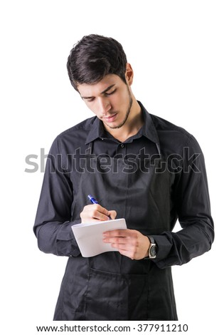 Young chef or waiter posing, wearing black apron and shirt, writing order on notepad, isolated on white background - stock photo
