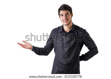 Young chef or waiter posing, welcoming guests with a smile, wearing black apron and white shirt isolated on white background - stock photo
