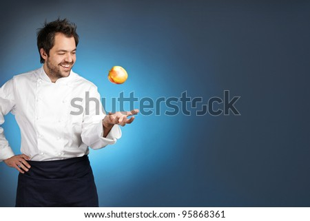 Young chef playing with apple agaist blue background
