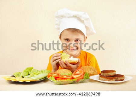 Young chef puts salad on the big sandwich - stock photo