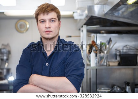 young chef stand keeping arms crossed in kitchen - stock photo