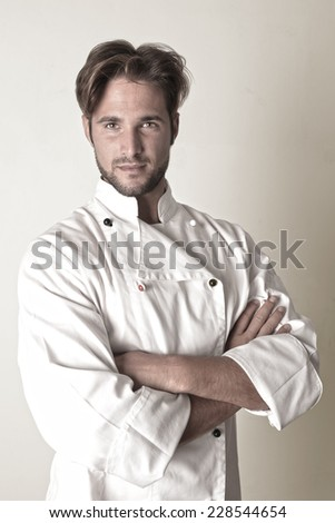 Young chef standing with arms crossed  - stock photo
