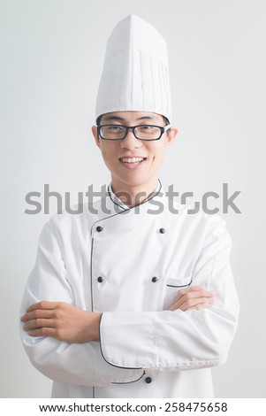 Young chef with arms crossed smiling - stock photo