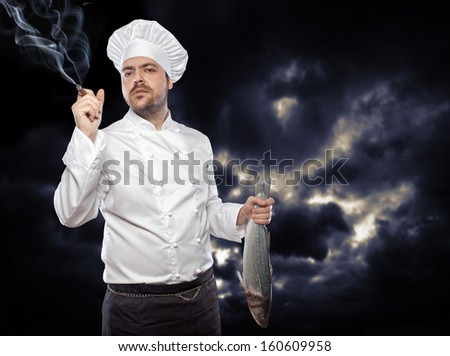 Young  chef with sea bass fish smoking cigar against dark sky