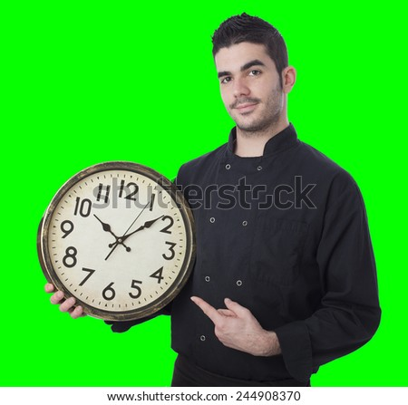 Young cheff holding a clock on green screen - stock photo