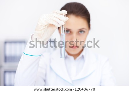 Young chemical female researcher holding glass tube with blue fluid in laboratory - stock photo